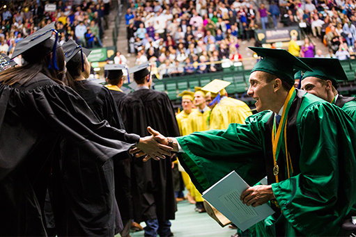 Graduates file into commencement, slap hands