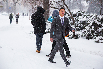 Student in business suit walking through snow