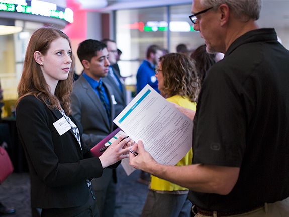 Student talks with employer at career event
