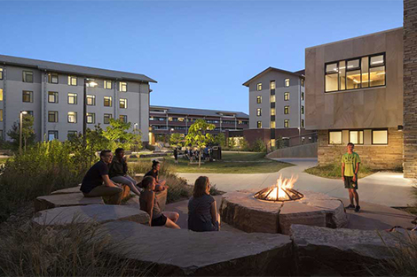 Students gathered around fire pit on campus