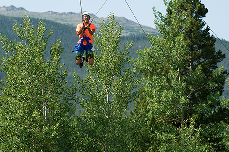 A high school student on the ropes course in mountains