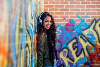 A girl wearing headphones lens against a brick wall covered in graffiti
