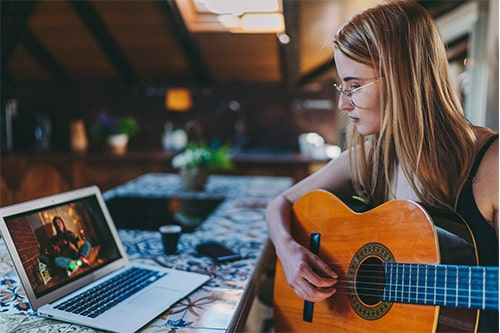 A girl plays a guitar in front of her laptop