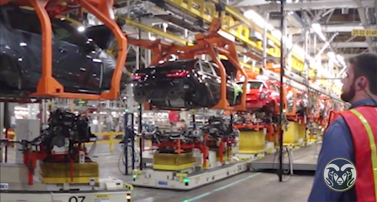 Man looking at cars in factory with link to video
