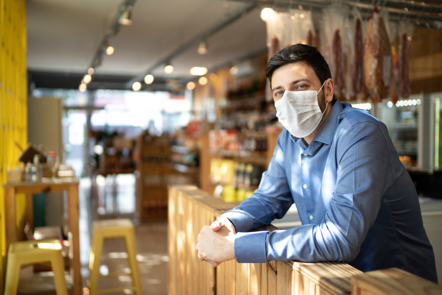 man standing in business wearing a covid-19 mask