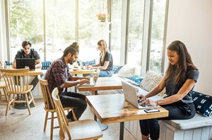 Online MBA students work in a cafe