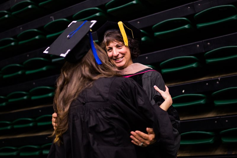 Margarita Lenk congratulates a student during commencement for the College of Business.